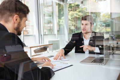 Chefe e colaborador formalizando o acordo de trabalho para evitar processos trabalhistas